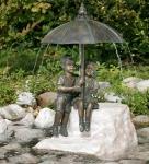 Rottenecker Bronzefigur Schirmpärchen midi mit Rosario Findling, Junge rechts, wasserspeiend